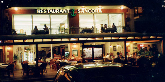 Photograph of the facade of the restaurant at night